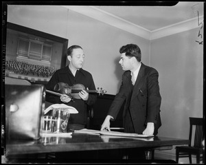 Jascha Heifetz showing a student, Raphael Silverman, how he would finger a difficult bar of music