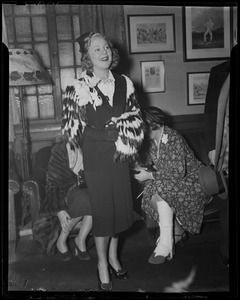 Sonja Henie at party, with others nearby
