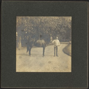 Ashdale Farm. Man standing with horse in driveway, possibly Otto Kunhardt.