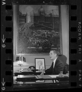 Mayor of Boston Kevin White sitting at desk with a large painting above