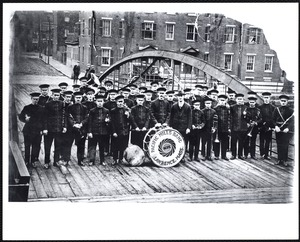 Pacific Mill Band standing in front of entrance to Upper Pacific Mills